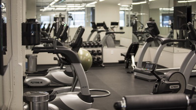 Fitness room that includes treadmills, elliptical machines, rowing machines, Peloton bikes and a multi-gym.