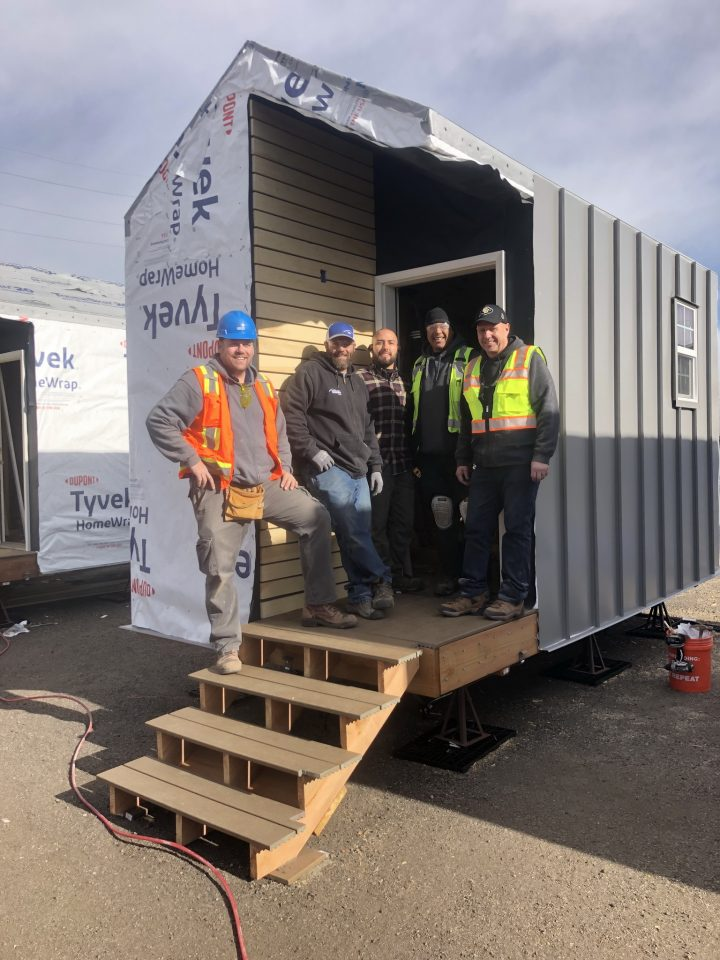 Colorado Doorways Account Manager Brian Phillips, Field Service Technicians Jeff Squillace, Carlos Mijares and Marcus Hall and Vice President of Operations Keith Rigli take a break from installing doors in new homes at Beloved Community Village.